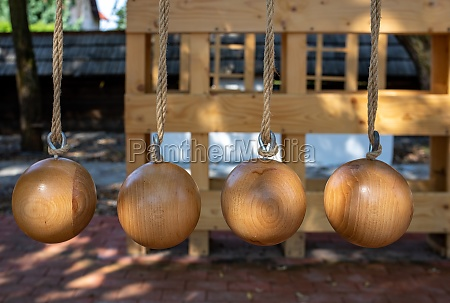 wooden balls hanging on ropes