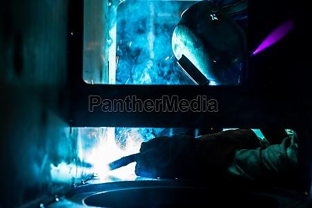 welder working in industrial metal factory
