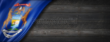 michigan flag on black wood wall