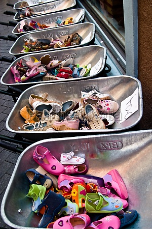children shoes in wheelbarrows