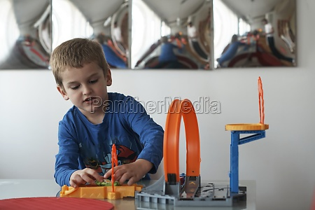 father and children playing car toy