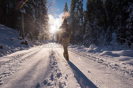 young photographer walking on snowy country