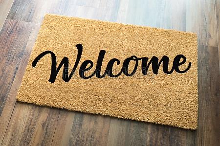 tan welcome mat on wood floor