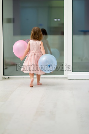 cute little girl playing with balloons