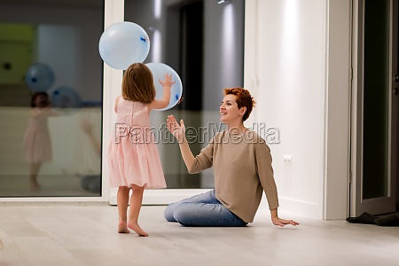 mother and cute little daughter playing