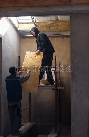 roofer man installing thermal insulation layer
