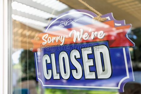 storefront closed sign through window