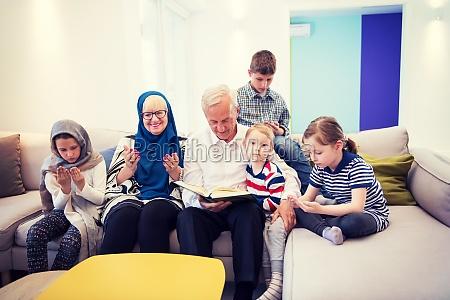 modern muslim grandparents with grandchildren reading