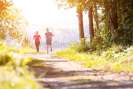 young couple jogging on sunny day