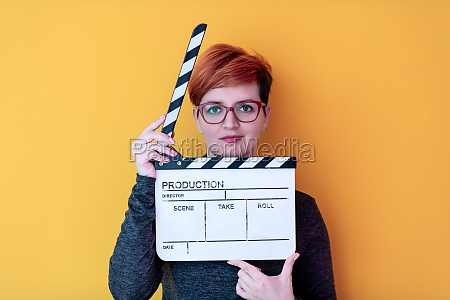 woman holding movie clapper against yellow