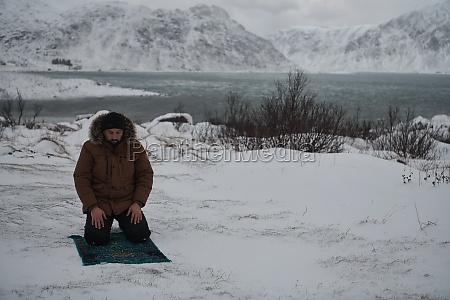 muslim traveler praying in cold snowy