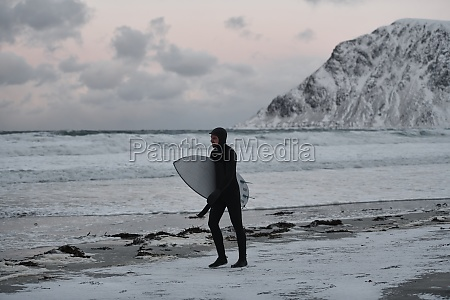 arctic surfer going by beach after