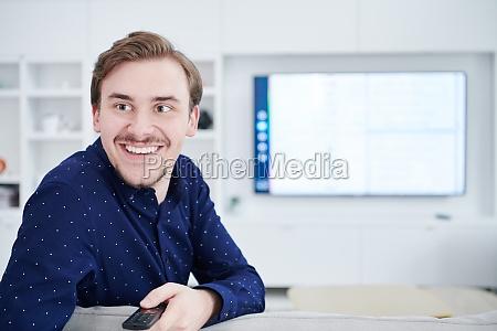young man watching tv at big
