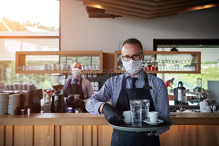 waiter in a medical protective mask