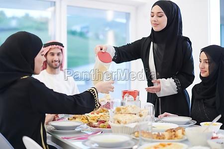 muslim family having iftar dinner drinking
