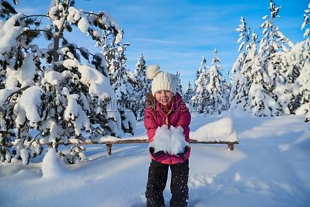 girl throwing fresh snow at beautiful