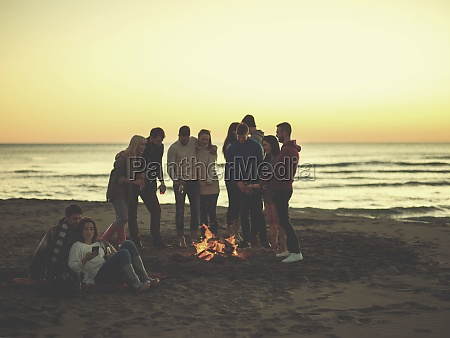 couple enjoying bonfire with friends on