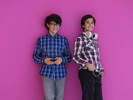 arab teenagers against pink wall