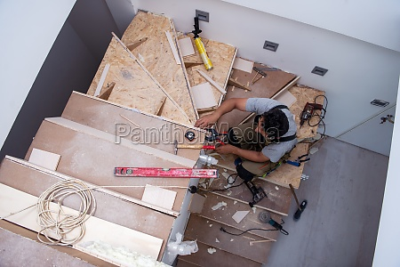 carpenter installing wooden stairs