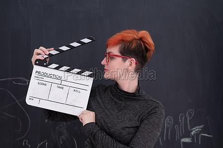 redhead woman holding clapper on black