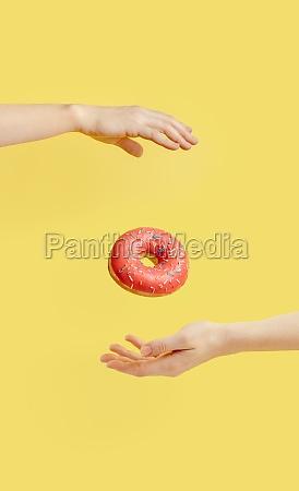 donut falls between hands on yellow