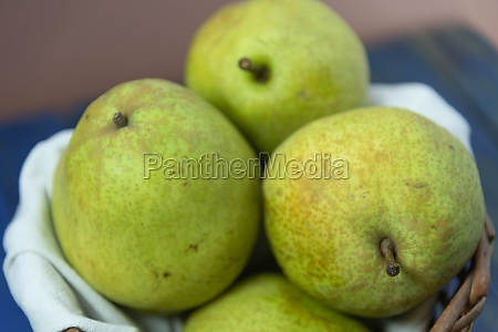 green pear fruits in wooden basket