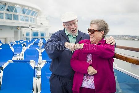 senior couple fist bump on deck