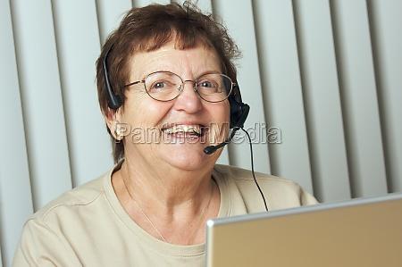 smiling senior adult with telephone headset