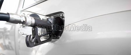 black diesel gas pump nozzle filling