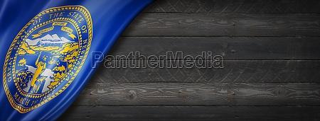 nebraska flag on black wood wall