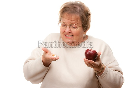 confused senior woman holding apple and