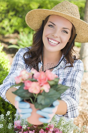 young adult woman wearing hat gardening