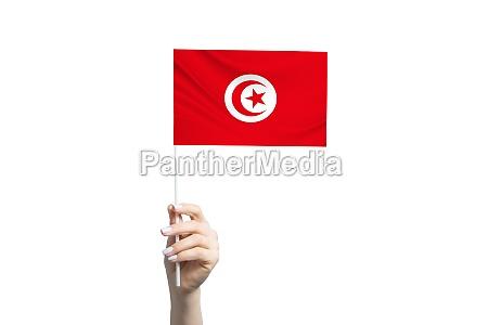 beautiful female hand holding tunisia flag