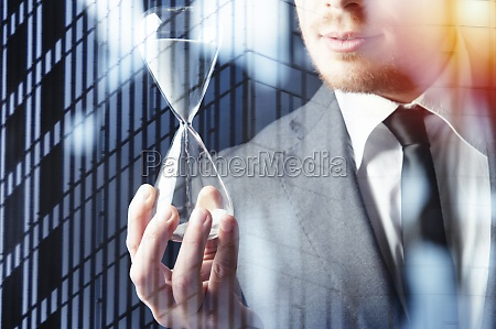 businessman holding a hourglass concept of