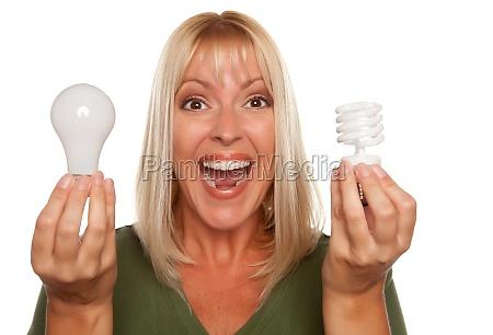 woman holds energy saving and regular