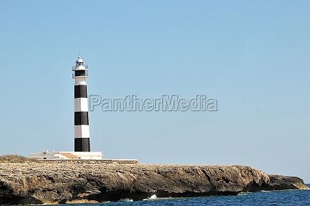 rocky coast with lighthouse on menorca