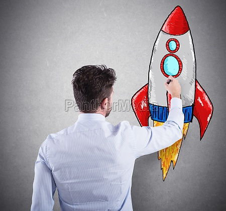 businessman drawing a rocket concept of