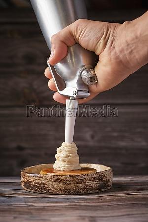 chef using cream whipper and garnishing