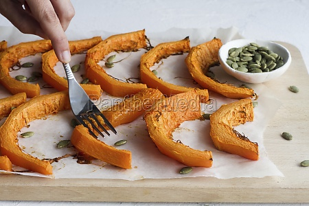 hand with fork smashing baked pumpkin