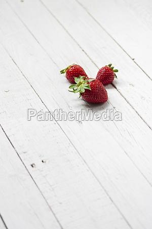 fresh strawberries on white wooden plank