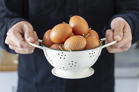 man holds brown chicken eggs in