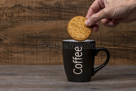 person holding cookie over black mug