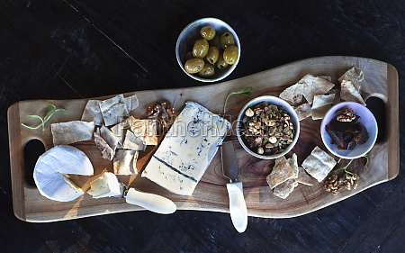 a cheese platter with nuts olives