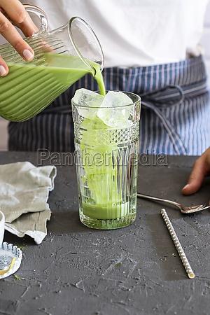 woman pours matcha tea into a