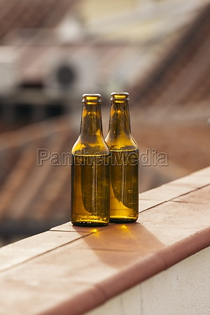 two beer bottles on balcony wall