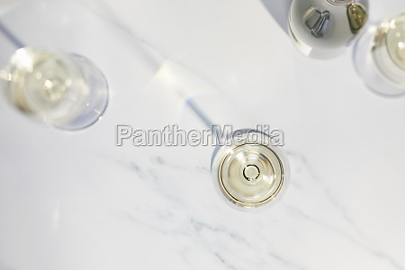 three white wine glasses and a