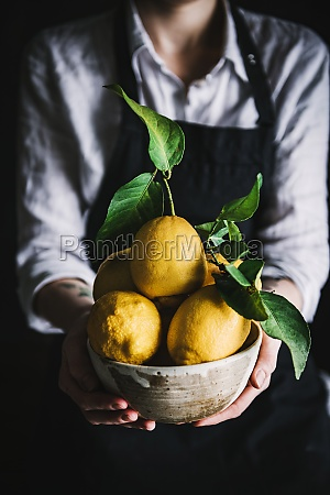 woman holding bowl with lemons