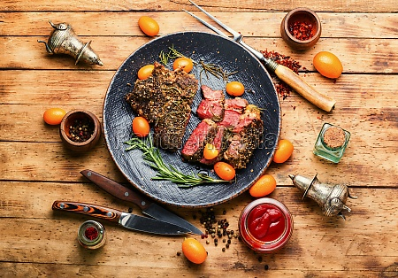 freshly veal steak with kumquat wooden