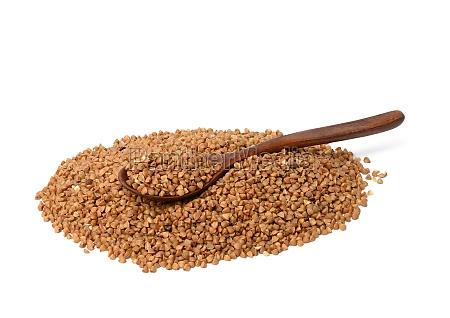 raw buckwheat grains in wooden spoon