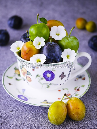 three different plums in a cup